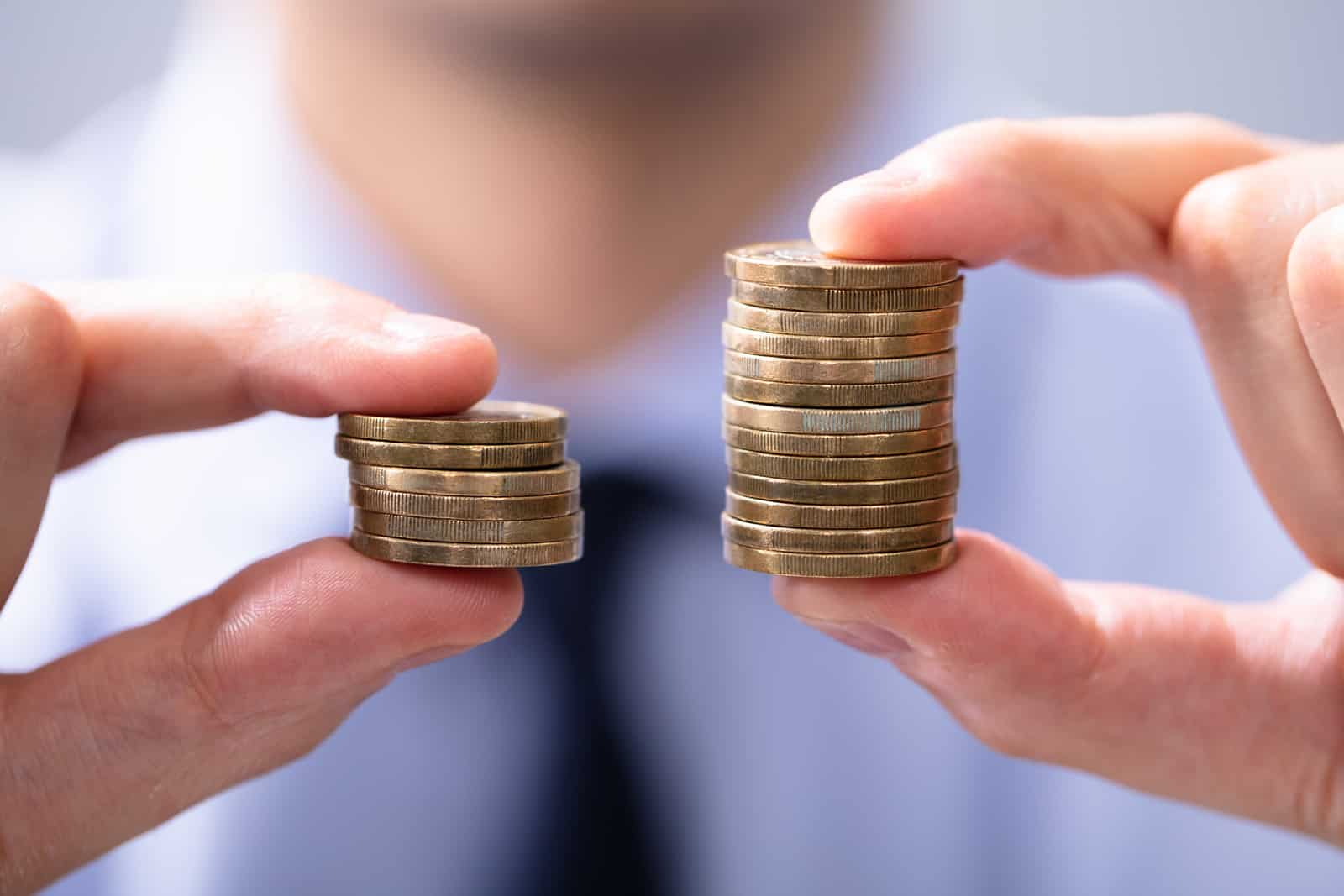 Man Holding Two Coin Stacks To Compare