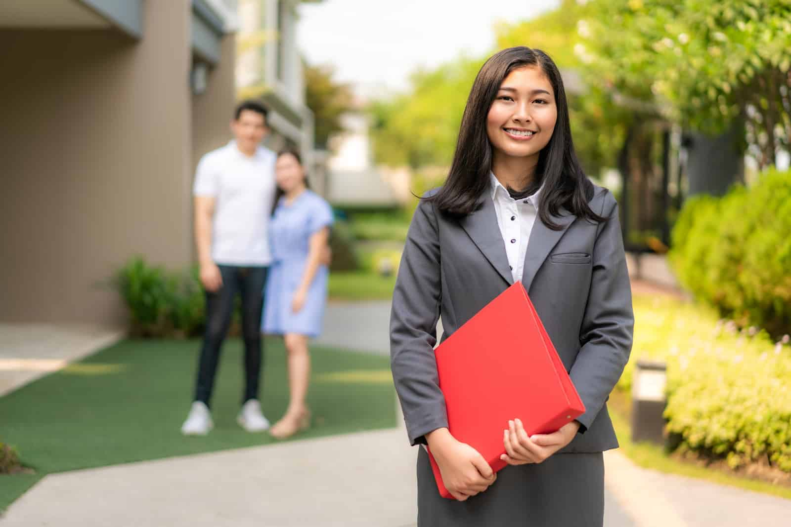 """Asian confident woman real estate agent or realtor in suit holding red file and smile with young couple home sellers behind in front of house. Portrait of a lovely female broker.""""r"""